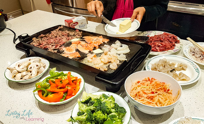 Table setting with all of the ingredients for Vietnamese butter beef and meat on the grill