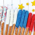 These Red White and Blue Dipped Pretzel Rods are perfect for summer and outdoor BBQ's. And don't forget about the 4th of July! Everyone will love the look and taste of this delicious dessert recipe, and they'll also look pretty festive on the table as well! #redwhitebluepretzelrods #dessert #4thofJuly #desserts #pretzeldesserts