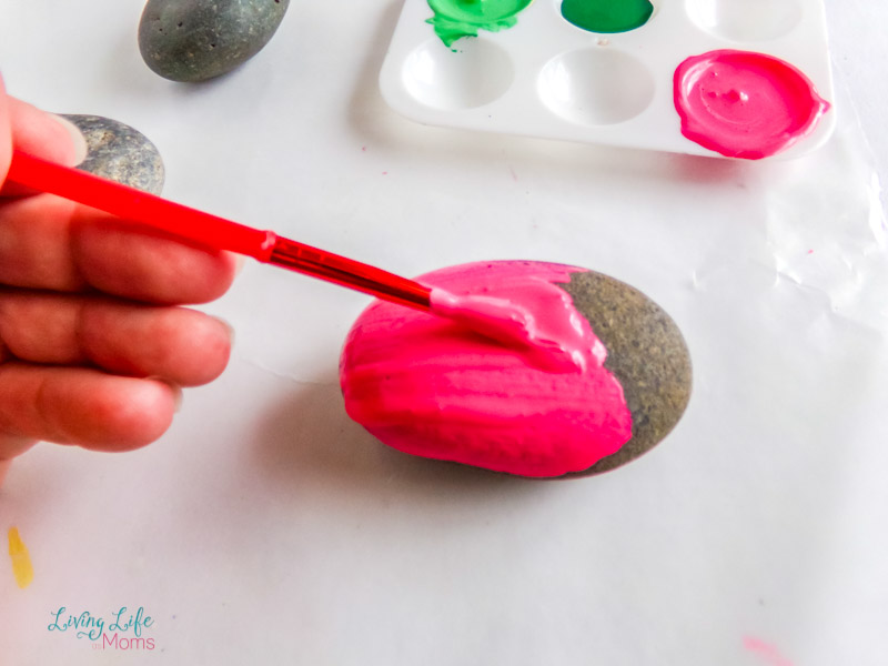 Painting a rock with pink paint with a paintbrush