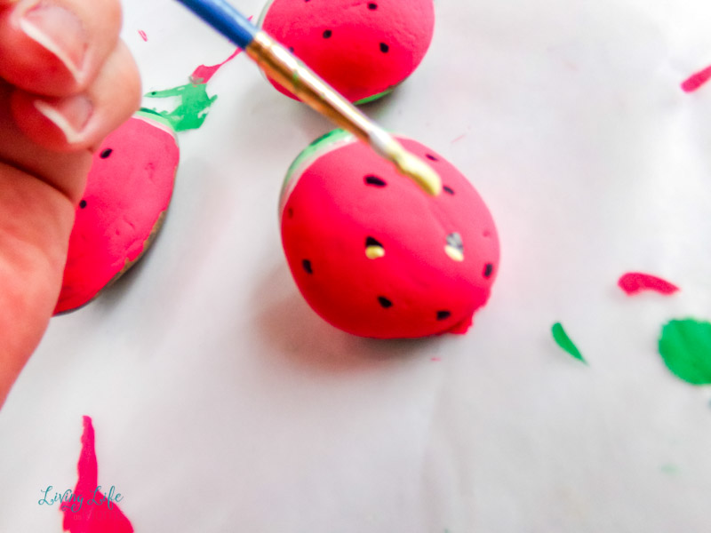 Adding white paint to the black seeds for the watermelon painted rocks