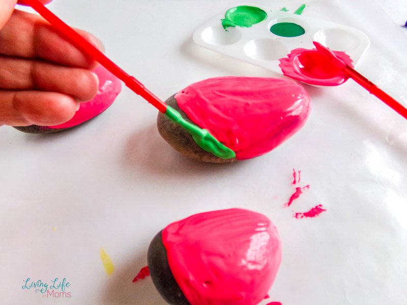 painting the green onto the bottom of the watermelon painted rock with a paintbrush.